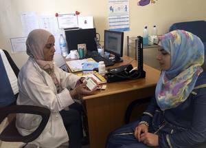 نور، وهي لاجئة من فلسطين تعيش في الأردن، في زيارة إلى مركز صحي مخيم عمان الجديد في عمان، الأردن، لتلقي المشورة والحصول على رعاية ما قبل الحمل من قبل قابلة قانونية من فريقها لصحة العائلة. الحقوق محفوظة للأونروا، 2015. تصوير أكيكو تاكيوشي
