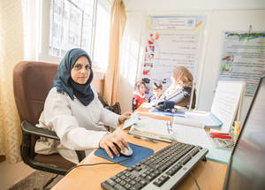 An UNRWA doctor attends to a mother and her two children in the UNRWA Rimal Health Centre in Gaza City. As part of the FHT implementation, e-Health, an electronic patient record system, was introduced to UNRWA clinics, significantly improving efficiency in the delivery of health care services. © 2016 UNRWA Photo by Hussein Jaber