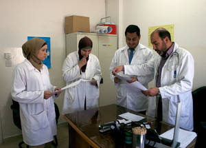 Members of one of the three Family Health Teams at the Amman New Camp Health Centre in Amman, Jordan, meet to discuss a patient case. Thanks to the generous support of donors, including the United States, UNRWA marked the full implementation of the Family Health Team approach in all of the 117 UNRWA health centres in Jordan, Lebanon, Gaza and the West Bank and six health centres in Syria this month. © 2014 UNRWA Photo
