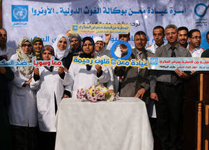 "A group photo of UNRWA Maen Health Centre staff and Dr. Isa Saleh, UNRWA Field Disease Control Officer, who contributed to the diabetes day activities holding a sign ""together against diabetes"" in the Health Centre in Khan Younis, southern Gaza. © 2016 UNRWA Photo by Rushdi Al Sarraj"