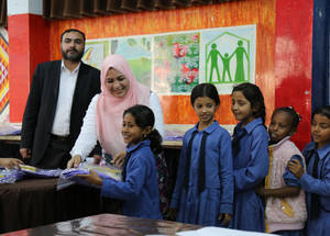 The Chalhoub Group Corporate Social Responsibility (CSR) Executive, Najlaa Ashrour, helps distribute the bags to students at the Jerash Girls Preparatory School in Jordan  © 2016 UNRWA Photo by Ahmad Abu Haweleh