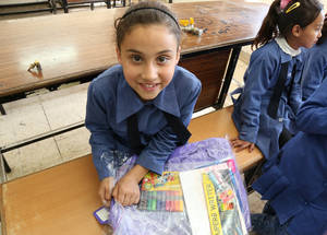 """I will change my old bag with this one for sure! It's my favorite color,"" says third-grader Salsabil. © 2016 UNRWA Photo by Ahmad Abu Haweleh"