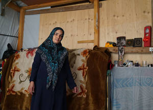 "The conflict in Syria has forced thousands of Palestine refugees to flee to Lebanon in search of safety; however, the living conditions can be harsh, especially in the winter.  ""Last night, we were sleeping in the living room. When it started raining, water leaked from the roof, soaking the floor,"" explains Raya Awada, standing in her makeshift shelter where she lives with four family members. Beqaa Valley, Lebanon. © 2016 UNRWA Photo by Christien van den Brink"