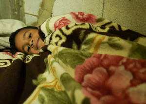 "Hadi Ma'moun Mersal lives with five members of his family in a single room.  ""We use our blankets and clothes to keep warm. But it is not enough,"" explains his father. Beqaa Valley, Lebanon © 2016 UNRWA Photo by Christien van den Brink"