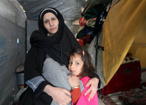 "Aisha is 38 years old and lives together with her husband and three children in Khan Dunoun shelter. ""The cold really kills us. Last night, when my daughter was trying to sleep, she woke me up shouting. I lit the kerosene heater to provide her warmth, but it was empty"". Khan Dunoun, Syria. © 2016 UNRWA Photo by Taghrid Mohammad"