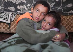 """على الرغم من المشقة والحزن، يقول علي، ابن أمينة، بأنه يواجه انخفاض درجات الحرارة بالتفكير في عائلته. على الرغم من شعور الصبي البالغ من العمر 13 عاما بالبرد، إلا انه لا يمانع من خلع سترته الوحيدة واعطائها لأخته الصغيرة. ويقول علي: """"في كثير من الأحيان، أغني محاولاً أن أنسى وضعنا البائس"""". خان دنون، سورية. الحقوق محفوظة للأونروا 2016، تصوير تغريد محمد"""