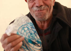 """My wife and I look forward to receiving the food basket. Our favourite ingredients are the lentils, the rice and the pasta,"" says Khamis Ali, a 65-year-old internally displaced Palestine refugee from Yarmouk refugee camp in Syria. Khamis Ali, Alliance distribution centre, Damascus, Syria. © 2016 UNRWA Photo by Taghrid Mohammad"