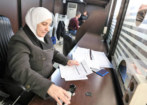 """We have between 200 and 300 families coming to pick up their assistance every day,"" says Maysam, who works at the distribution center at the UNRWA Damascus Training Center. Around 70 percent of the refugees use the assistance to pay for rent. For many, it is their only source of income. ""It helps them continue their life in a dignified way,"" she says. © 2018 UNRWA Photo by Iyad Faouri"