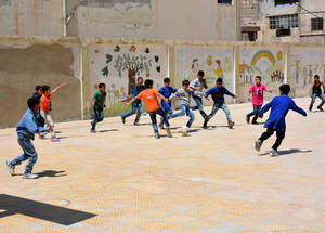 UNRWA schools not only provide a place to learn, but also a safe space to play with friends.   At this newly reopened school in Sbeineh camp, boys play football during a break. © 2018 UNRWA Photo by Fernande van Tets
