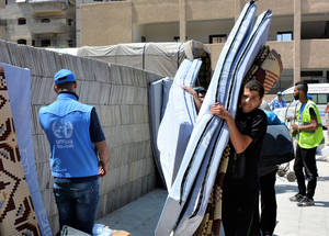 A Palestine refugee from Yarmouk receives mattresses for his family at a distribution point in Yalda. © UNRWA 2018 Photo by Iyad Faouri