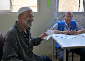 """Helmi Ahmad Mahmoud (55) has not been able to see his family; his wife, daughters and son, since they fled Yarmouk in 2012. He stayed behind and suffered under the siege. """"We had to eat local herbs boiled with spices."""" His mobile phone has become his most valued possession; it allows him to stay in touch with his family, who are now in Qabr Essit camp. The family relies on UNRWA cash assistance to survive. """"We live in poverty and struggle to make ends meet. We have adapted and gotten used to hardship."""" © UN"""