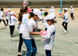 An UNRWA student helps a younger peer balance water balloons amidst a water fight at the UNRWA Balata Girls' School. © 2018 UNRWA Photo by Iyas Abu Rahma
