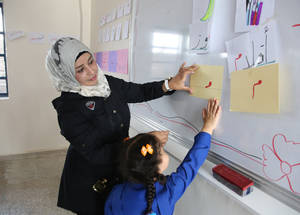 """Teaching is an incredibly rewarding job,"" says Muneera Malkash, who teaches at al-Houleh School in Khan Dunoun camp. Like most UNRWA teachers, she was an UNRWA student herself in the past. ""In my experience, what keeps students motivated is a motivated teacher. If you have a passion for teaching, your students are more likely to show a passion for learning.""  © 2018 UNRWA Photo by Taghrid Mohammed"