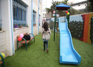 Twelve-year-old Lina Luay Zaq (grade 7) walks through the new playground at Birzeit Girls' School. A new slide, swings, benches in the playground and surrounding murals substantially enhanced the school environment. © 2018 UNRWA Photo by Dina Sharif