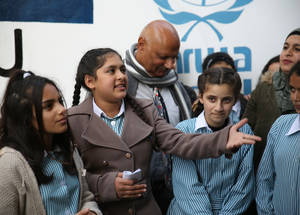 Seventh-grader Abrar Mousa Dalalsheh (center, 12) addresses UNRWA West Bank staff and her peers, noting the techniques students used to adapt recycled material for their eco-friendly garden. © 2018 UNRWA Photo by Dina Sharif