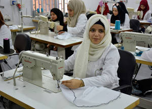 "The room where they teach fashion technology in Homs has been laid out like a factory hall, to prepare students for a possible future working environment. ""I have always loved sewing and I dream of becoming a fashion designer,"" says Ghena (16). © 2018 UNRWA Photo by Fernande van Tets"