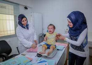 Little Lana Abu Sweid is not so happy to be weighed. UNRWA supports new mothers with prenatal and antenatal care, growth monitoring, vaccinations health check-ups as well as providing them with a baby kit. In 2018, 7,450 Palestine refugee mothers gave birth. © 2018 UNRWA Photo by Ahmad Abo Zaid