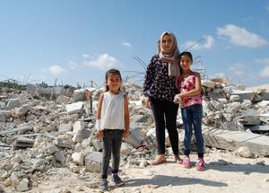 Ilham and two of her children, Talin (8) and Raghad (5) stand outside the twisted remains of their former house in al-Walajeh. The home was demolished by the Israeli authorities in September 2018.