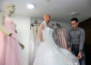 "Ra'ed has taken out 12 UNRWA loans so far, the latest for 400,000 SYP, around US$ 1,000. He uses these loans to purchase tulle and other fabric, as well as sequins. He makes these purchases in the winter when business is slow, and pays off the loans after the summer wedding season. ""Thankfully people still get married, despite the crisis, but they do not spend as much on a dress as they used to,"" he says. © 2019 UNRWA Photo by Taghrid Mohammad"