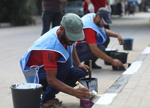 As part of the environmental cleaning campaign of Palestine refugee camps ahead of the Eid al-Adha campaign, labourers paint the side-walk curbs in Nuseirat camp in the Gaza Strip. The environmental cleaning campaign is generously funded by the Kingdom of Saudi Arabia through the Saudi Fund for Development. #UNRWA #SFD #forPalestinerefugees © 2019 UNRWA Photo