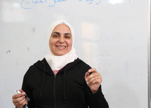"For Amal Nassar (أمل نصار) teaching is important contributions to improving the lives of children and to help them fulfill their potential. ""It is a field filled with challenges. Teachers must be patient and understanding."" A second-grade teacher with a degree in Arabic literature, Amal joined UNRWA as a daily paid class teacher in 2016.  ""I am passionate about teaching languages and I have a passion for Arabic, in particular.  My love of communication with children draws me to teaching,"" she notes. Amal draws inspiration from her university professor's diligence and direction: ""I always enjoyed having him as my professor and I appreciate how approachable he was.  It has always been my dream to become a teacher and now I am following that dream at the UNRWA school,"" she says."