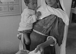UNRWA has been the main comprehensive primary health-care provider for Palestine refugees for 70 years. This includes the introduction of mother and child-care in the early 1950s, including ante and post-natal care, preconception and delivery care, as well as family planning services. An innovative phone app to track mother and child-care was introduced in 2017.  In this picture, a pregnant mother and her son present at an UNRWA health centre in Husn Palestine refugee camp in Jordan. © 1969 UNRWA Archive Photo by George Nehmeh. SDG 3 and SDG 5