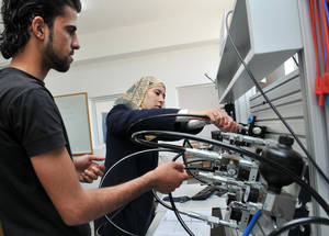 The Ramallah Women's Training Center (RWTC), opened in 1962, was the first vocational training center (VTC) for women in the Arab world. Today, there are eight VTCs for over 7,500 Palestine refugees across all five fields of Agency operation. As off 2018, the Agency graduated some 114,000 Palestine refugee students from its vocational training centers Employment rates for TVET graduates are high, helping to mitigate youth unemployment, including among women. Currently, women make up over 40 per cent of the student body, thus improving the prospect of equal economic rights and opportunities.  This photo shows a female and male student using laboratory equipment at the Gaza Vocational Training Centre. © 2009 UNRWA Photo by Shareef Sarhan. SDG 5 and SDG 8
