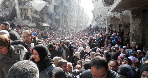 In January 2014, when UNRWA was able to complete its first humanitarian distribution in Yarmouk after almost six months of siege, it was met by thousands of desperate residents on the destroyed main street. © 2014 UNRWA Photo