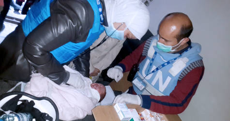 A doctor examines a tiny patient at a temporary health point in the besieged area of Yarmouk. UNRWA runs 12 health centers and 12 health points throughout Syria designed to cater to both settled and displaced Palestine refugee populations. This includes a temporary health point in the besieged area of Yarmouk, where this doctor examines a tiny patient. ©2015 UNRWA Photo