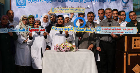 """A group photo of UNRWA Maen Health Centre staff and Dr. Isa Saleh, UNRWA Field Disease Control Officer, who contributed to the diabetes day activities holding a sign """"together against diabetes"""" in the Health Centre in Khan Younis, southern Gaza. © 2016 UNRWA Photo by Rushdi Al Sarraj"""