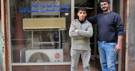 Mustafa Dibben stands with his employer Tala Taher outside the air-conditioning shop in Homs, Syria. Mustafa secured a job after completing an UNRWA vocational training course. ©2018 UNRWA Photo by Fernande van Tets