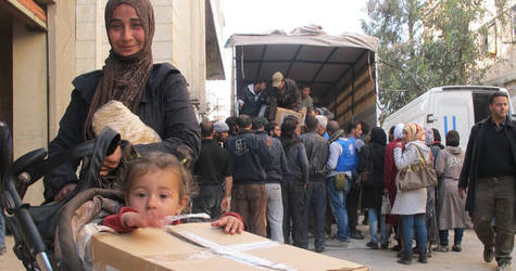 A mother and child receive UNRWA food assistance at the distribution areas in Yalda, 14 April 2015. © UNRWA Photo