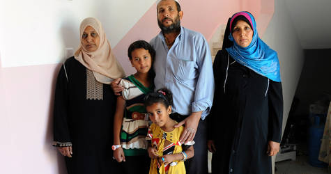 """""""In this house, we can invite guests and offer them tea,"""" said Nabil Abu Musa about his family's new home in the Khan Younis Rehousing Project. Nabil co-signed the undertaking together with Fatheia (left) and Khadra (right), his two wives. © 2015 UNRWA Photo by Khalil Adwan."""