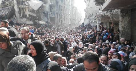 Palestine refugees crowd the main street of Yarmouk in February 2014, for the first UNRWA food distribution after six months of siege. ©UNRWA.