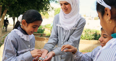 Thirteen-year-old Yasmin al-Najjar (centre), a student in the UNRWA Rehabilitation Centre for the Visually Impaired (RCVI), distributes snacks among her classmates, celebrating her first-place prize in the UNRWA educational human rights competition in Gaza City. © 2016 UNRWA Photo by Tamer Hamam