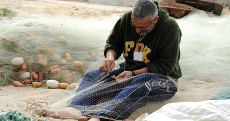 A JCP beneficiary is repairing fishing nets at the Gaza sea port. © 2014 UNRWA Photo by Shareef Sarhan