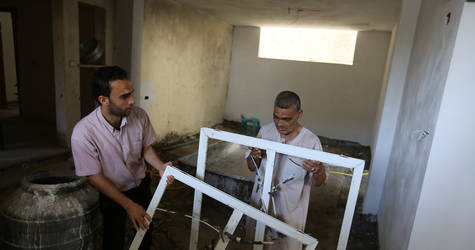 Rafat Khurais and his son in their damaged home in Maghazi camp in Gaza. © 2016 UNRWA Photo by Tamer Hamam.