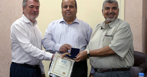 Mr. Bo Schack, Director of UNRWA Operations in Gaza, and Mr. Farid Abu Athra, Chief of UNRWA's Education Programme in Gaza, honour one of the school principals for his 40 years of service. © 2016 UNRWA Photo by Tamer Hamam