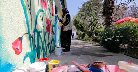 Artist Israa' Musallam, 28 years old, is drawing on the walls of the UNRWA Gaza Field Office. © 2017 UNRWA Photo by Rushdi Al Sarraj