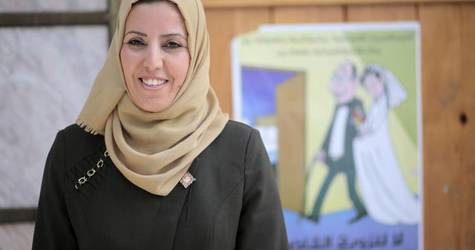 Lawyer Hayat Mahmoud standing in front of a poster distributed during the 'Girls Not Brides: End Child Marriage' initiative in the Al-Daraj Women's Programme Centre in Gaza City. © 2017 UNRWA Photo by Rushdi al-Saraj