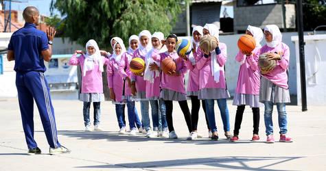 """مجموعة من طالبات مدرسة البريج الإعدادية """"ب"""" للبنات خلال جلسة تدريب كرة السلة، كجزء من مبادرة """"تمكين الفتيات من خلال الرياضة"""" المنفذة من قبل برنامج الإغاثة والخدمات الاجتماعية في الأونروا في عدد من مدارسها في غزة. الحقوق محفوظة للأونروا 2017، تصوير خليل عدوان"""