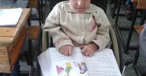 صورة  الطالبة / رشا  كمال اللوح ,الصف الثالث ,  مدرسة دير البلح الابتدائية ء  , هكذا وضع الطالبة  في الفصل اثناء الدراسة قبل توفير المقعد الخاص بالكتابة علي الكرسي المتحرك