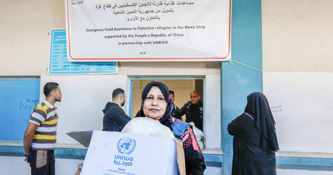 Naeima, a 50-year-old woman Palestine refugee, collects a food parcel from the UNRWA food distribution centre in Jabalia camp as a part of the emergency food assistance to the Palestine refugees in the Gaza Strip that is supported by the People's Republic of China in partnership with UNRWA. ©2018 UNRWA Photo by Mohammed Hinnawi.