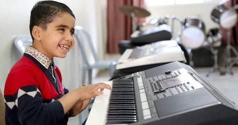 محمد علوان يعزف على البيانو الكهربائي خلال حصة الموسيقى في مركز الأونروا لإعادة تأهيل الأشخاص المعاقين بصريا في غزة. الحقوق محفوظة للأونروا، 2018. تصوير خليل عدوان