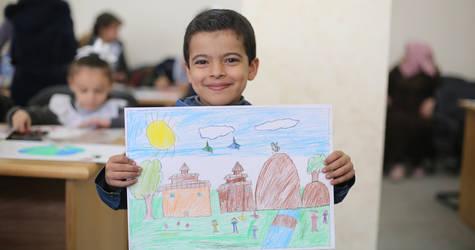 """أحد الطلاب يعرض لوحته التي شارك فيها خلال المسابقة الفنية  """"السلام مع اليابان """" في كلية غزة للتدريب . جميع الحقوق محفوظة: © الأونروا غزة 2019،تصوير  إبراهيم أبو عشيبة."""