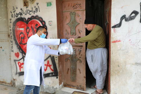 An UNRWA staff member provides medication to an elderly Palestine refugee. © 2020 UNRWA Photo