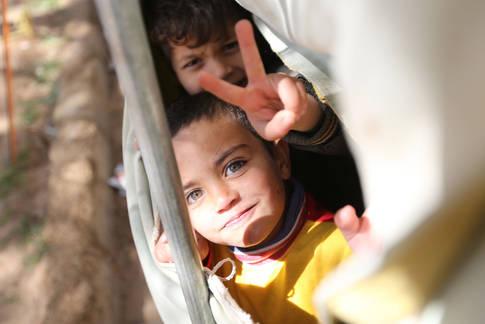 لاجئان فلسطينيان من سوريا في مخيمهما للاجئين في الأردن يبتسمان للكاميرا. الحقوق محفوظة للأونروا ، 2013 ، تصوير علاء غوشة