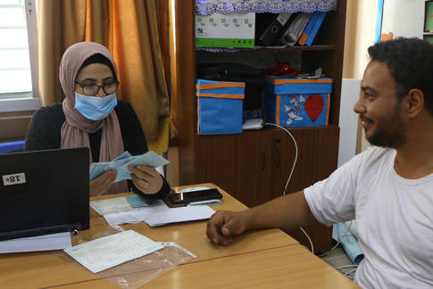 An UNRWA staff member conducts verification for emergency cash assistance in Beddawi camp © 2020 UNRWA photo by Maysoun Mustafa