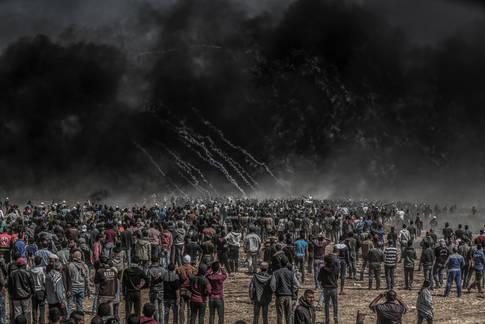 المتظاهرون الفلسطينيون يتجمعون في خزاعة على جانب السياج المحاذي من جهة غزة بين إسرائيل وبين قطاع غزة خلال مسيرة العودة الكبرى يوم 6 نيسان 2018. الصورة من عام 2018 بإذن من محمود بسام