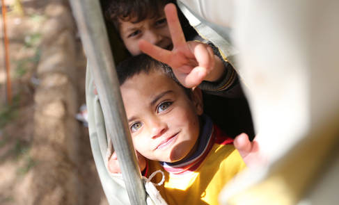 Two Palestine refugees from Syria in their refugee camp in Jordan smiling to the camera. © 2013 UNRWA Photo by Alaa' Ghosheh